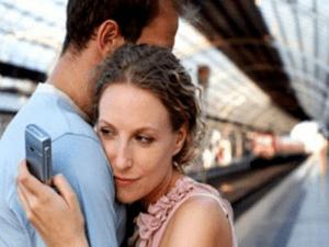 investigatore privato napoli : una donna mentre abbraccia il suo uomo e allo stesso tempo legge il proprio smartphone