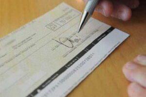 Immagine di un assegno bancario mentre viene firamto